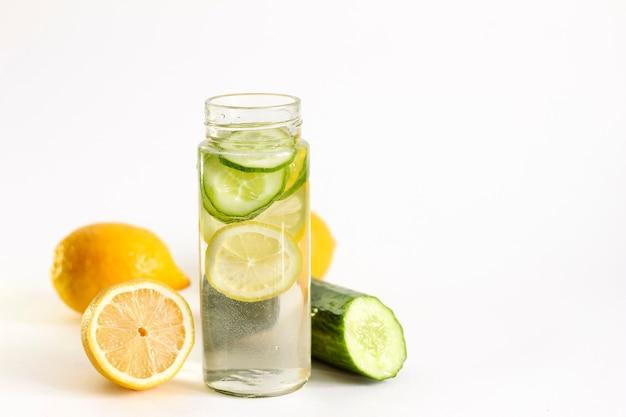 Água com limão e pepino em uma garrafa sobre um fundo claro. bebida desintoxicante.
