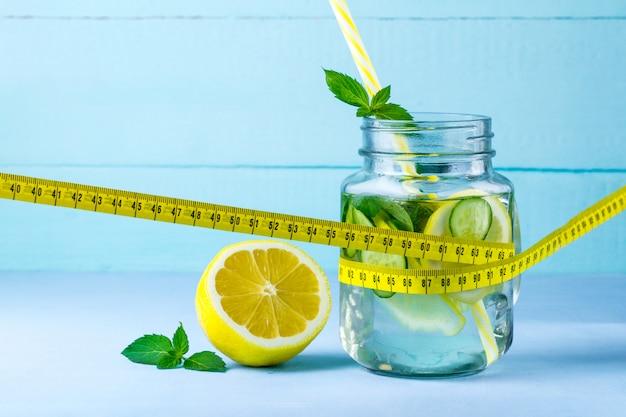 Água com limão, limão suculento, menta e fita métrica