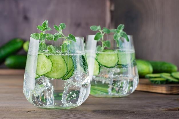 Água com pedaços de pepino e gelo em um copo transparente na mesa de madeira