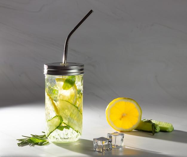 Água com pepino e limão em um copo de vidro com um tubo de metal