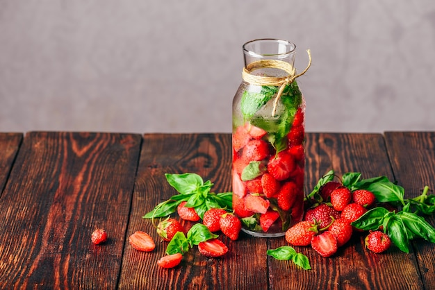 Água com sabor em garrafa com morango fresco e folhas de manjericão