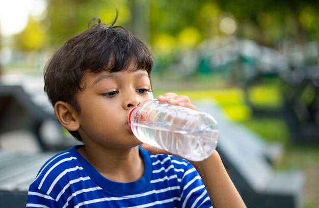Água com sede de criança asiática e água potável de uma garrafa de plástico transparente no parque.