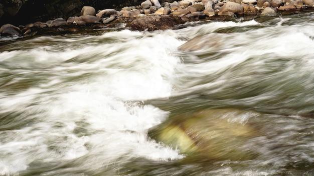 Água corrente de córrego rochoso. pedras na água. fundo natural