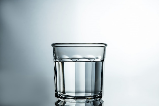 Água cristalina. água purificada em um copo sobre uma mesa cinza. conceito de água pura.