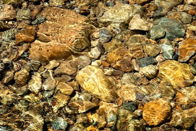 Água cristalina no rio e textura de pedra