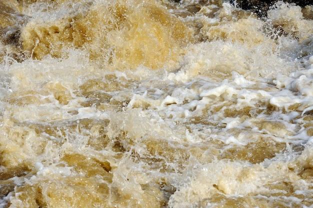 Água da inundação do rio com espuma branca