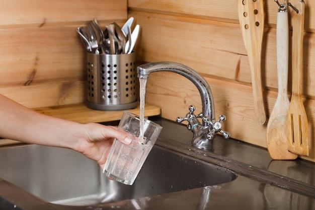 Água da torneira derrama água em vidro na mão feminina