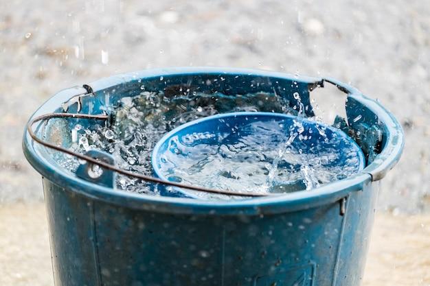 Água de chuva velha de dipper azul de balde