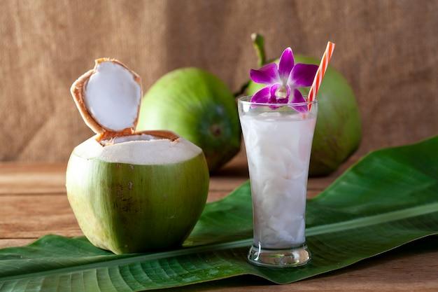 Água de coco fresca em um copo em uma placa de madeira para beber