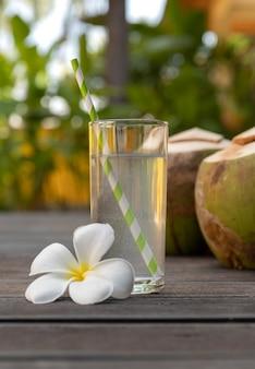 Água de coco fresca tropical em vidro decorado plumeria em fundo de madeira