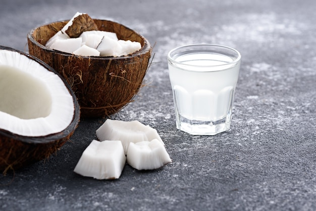 Água de coco moderna em vidro, metades de coco em cinza
