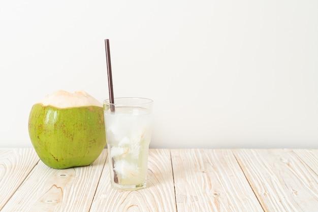 Água de coco ou suco de coco em copo com cubo de gelo