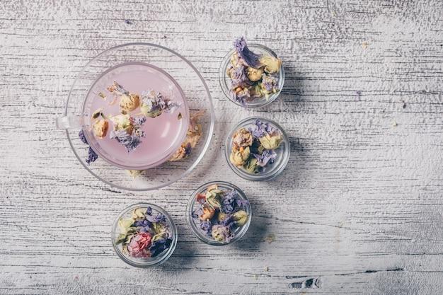 Água de cor roxa em um copo com vista superior de chá de flores secas em um fundo branco de madeira