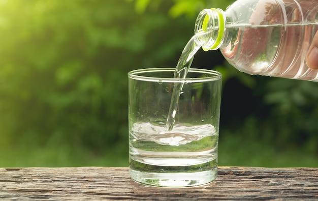 Água de derramamento da mão fêmea da garrafa ao vidro no fundo da natureza.