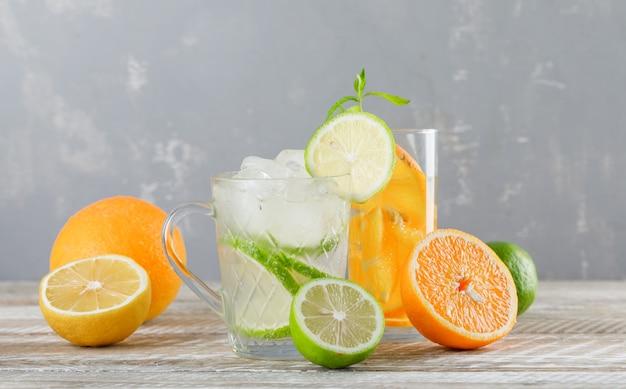 Água de desintoxicação com limas, limões, laranjas, hortelã no copo e copo na mesa de madeira, vista lateral.