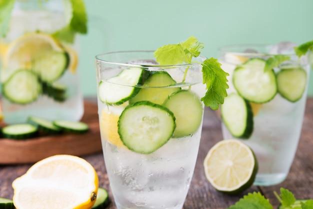 Água de desintoxicação refrescante com pepino, limão e hortelã fresca sobre um fundo verde claro. bebida orgânica, vegana.