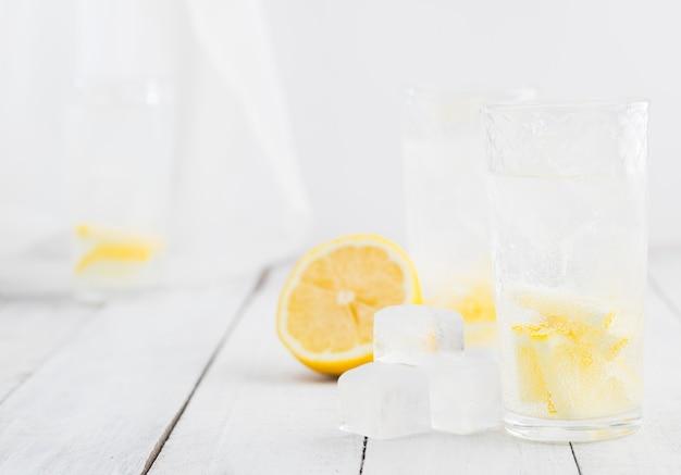 Água de detox de suco de limão. água mineral infundida com limões. mesa de madeira branca.