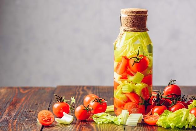 Água de limpeza com infusão de hastes de aipo e tomate cereja. ingredientes espalhados na mesa de madeira. copie o espaço à esquerda.