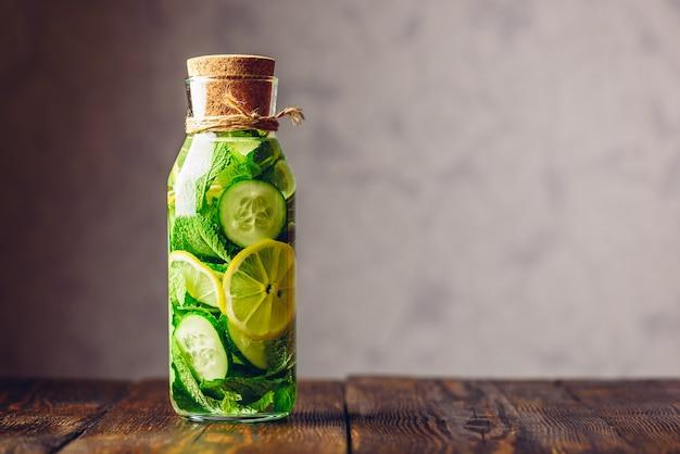 Água de limpeza infundida com pepino em fatias de limão e raminhos de hortelã fresca