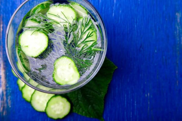 Água de pepino em vidro com endro em madeira azul. desintoxicação, dieta.