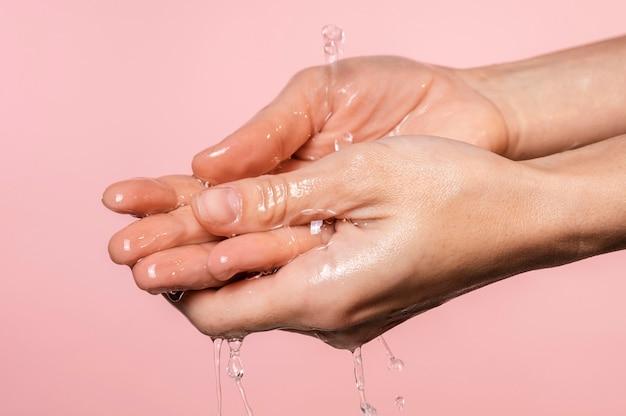Água derramada nas mãos da mulher, close-up