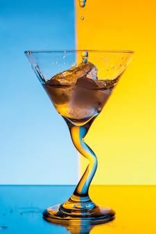 Água derramando em vidro sobre parede azul e amarela
