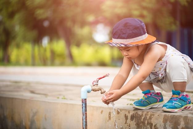 Água derramando nas mãos da menina. conceito do dia mundial da água