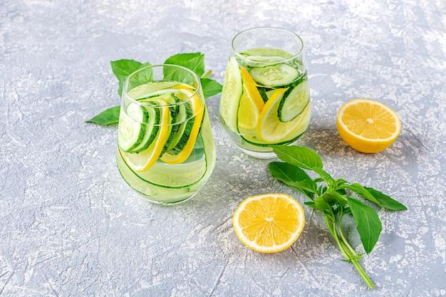 Água desintoxicação fresca bebida com pepino e limão. dois copos de limonada com folhas de manjericão e hortelã. conceito de nutrição adequada e alimentação saudável. dieta de fitness.