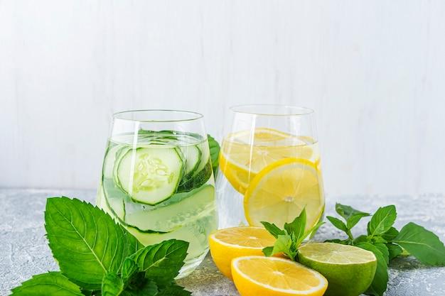 Água desintoxicação fresca bebida com pepino e limão. dois copos de limonada com hortelã. conceito de nutrição adequada e alimentação saudável. dieta de fitness. copie o espaço para o texto.