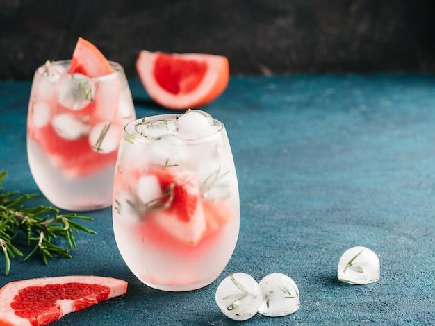 Água desintoxicada infundida ou coquetel alcoólico ou não alcoólico com toranja e gelo de alecrim em copo