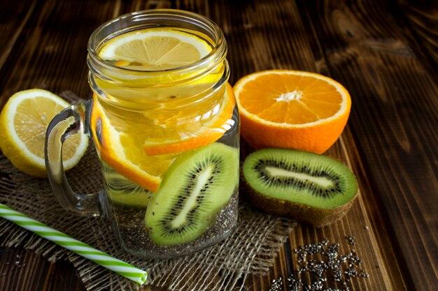 Água desintoxicante com chia e fruta na madeira rústica