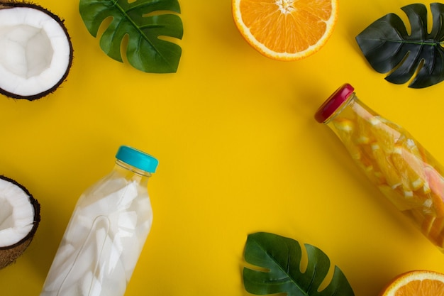 Água desintoxicante com coco e laranja nas garrafas de vidro no fundo amarelo. vista superior. copie o espaço.