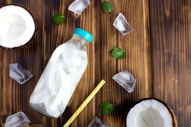 Água desintoxicante com coco no frasco de vidro no fundo de madeira marrom. vista superior. copie o espaço.