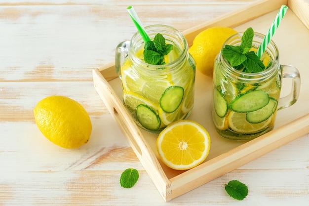 Água desintoxicante com fatias de limão e pepino em uma jarra na mesa de madeira.