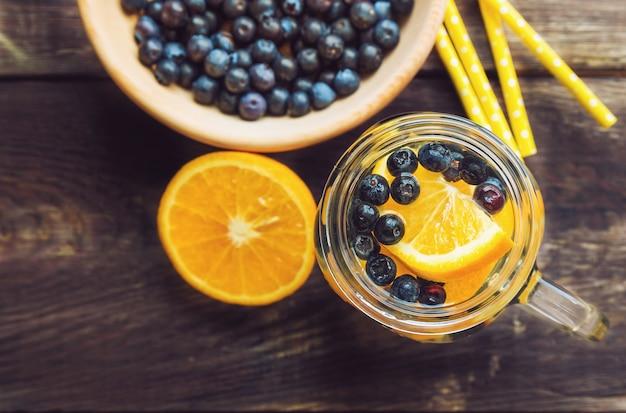 Água desintoxicante com laranja e mirtilos em jarra na superfície de madeira rústica. vista do topo.