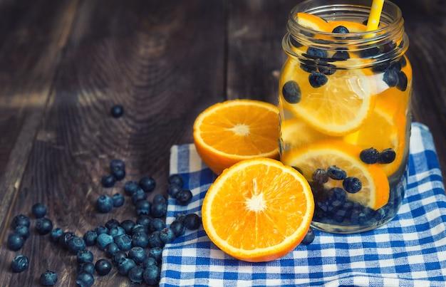 Água desintoxicante com laranja e mirtilos em jarra na superfície de madeira rústica.