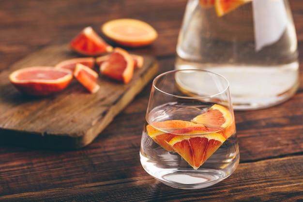 Água desintoxicante com laranjas de sangue no copo de bebida