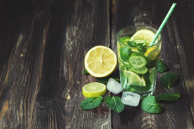 Água desintoxicante com limão, pepino e hortelã em superfície de madeira rústica