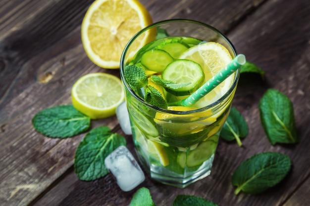 Água desintoxicante com limão, pepino e hortelã na mesa de madeira rústica. vista do topo.