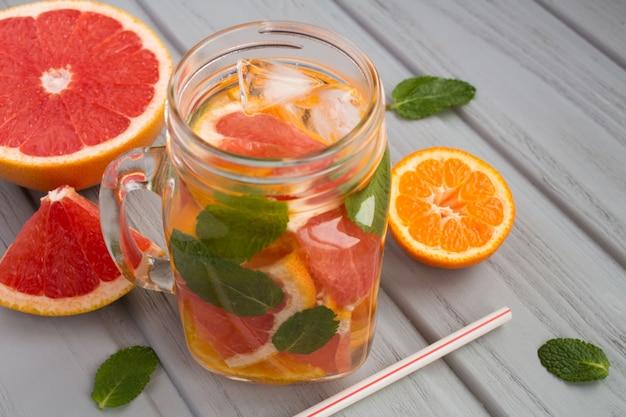 Água desintoxicante com tangerinas e toranja na superfície de madeira cinza