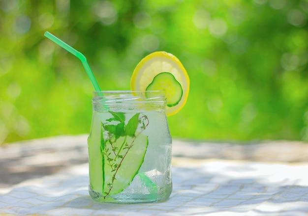 Água desintoxicante de pepino infundida com gelo. bebida refrescante de verão na mesa do jardim.