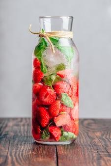 Água desintoxicante em garrafa com morango fresco e folhas de manjericão. orientação vertical.