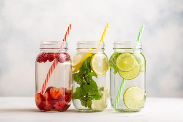Água desintoxicante em três potes com framboesas, limão, lima e hortelã
