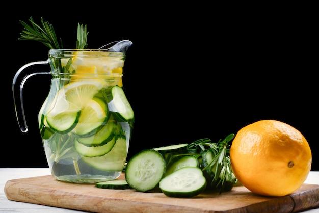 Água desintoxicante gelada e refrescante com limão, pepino, alecrim e gelo em frasco de vidro. copyspace. bandeira