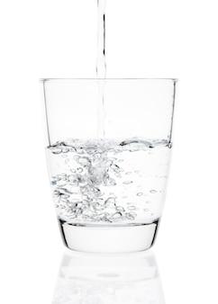 Água despejando em um copo isolado