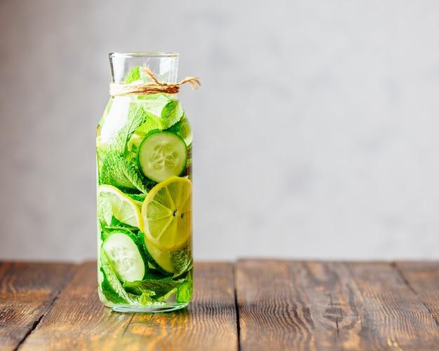 Água detox com infusão de limão fatiado, pepino e raminhos de hortelã. copie o espaço à direita.
