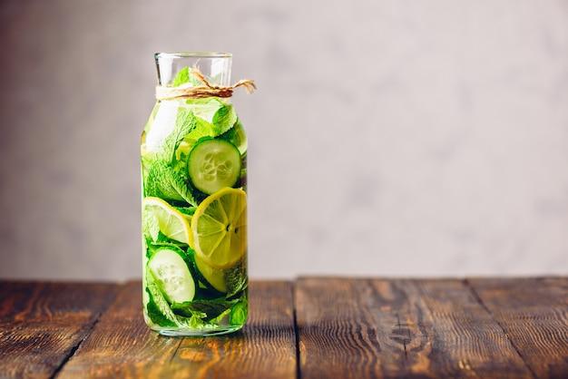 Água detox com infusão de limão fatiado, pepino e raminhos de hortelã fresca. copie o espaço à direita.
