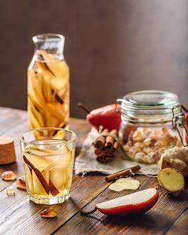 Água detox com infusão de pêra fatiada, pau de canela, raiz de gengibre e um pouco de açúcar. ingredientes na mesa de madeira