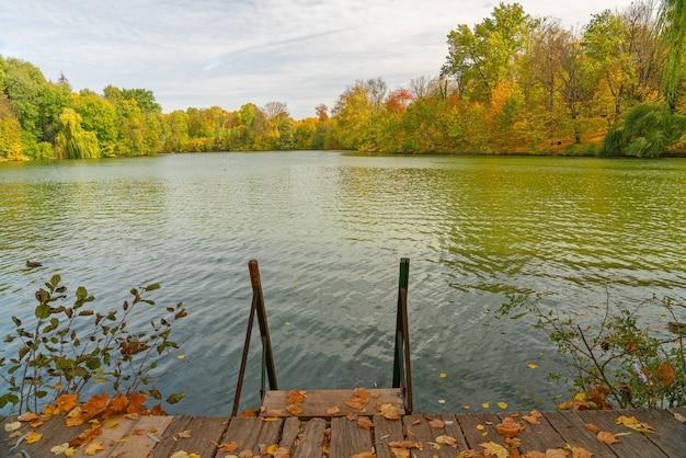 Água do lago no outono com degraus e paisagem de floresta pitoresca, parque sofievsky, uman