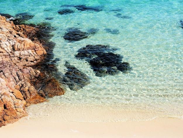 Água do mar azul límpida e areia branca com fundo de rocha marrom com vista para a praia